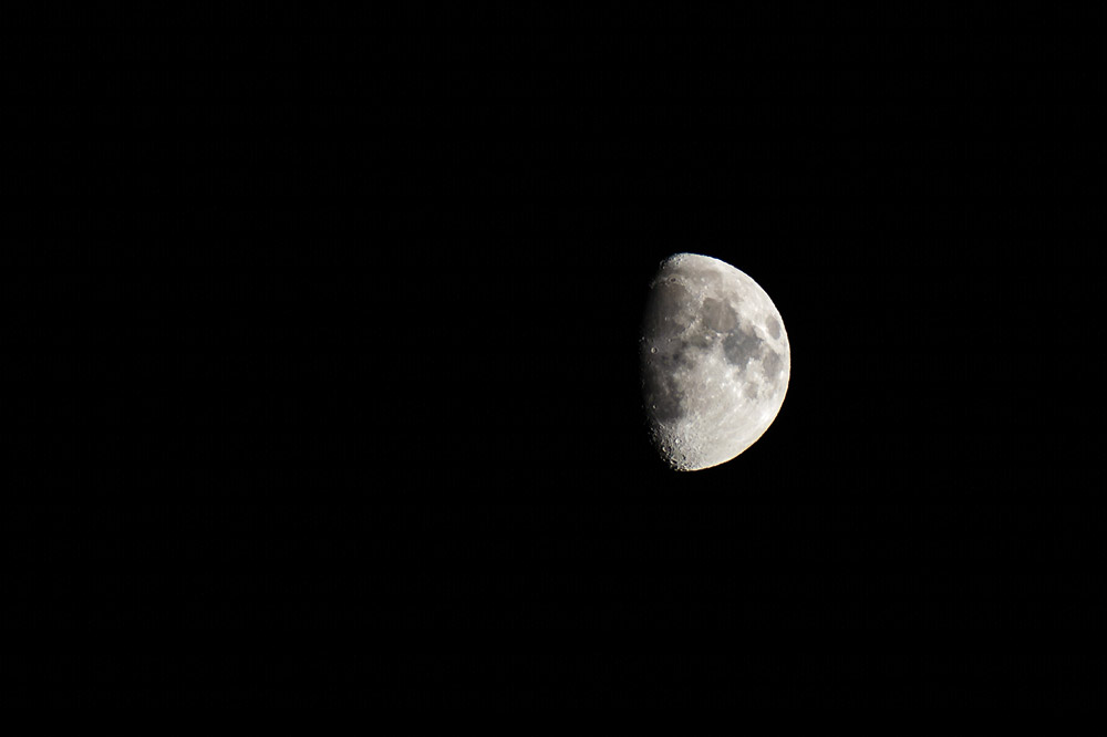"""Phase dite du """"premier quartier de lune"""". Photo recadrée pour que la lune paraisse plus grosse. Samyang 500mm - F/5,6 - 1/125 - ISO 200 © Clément Racineux / Tonton Photo"""