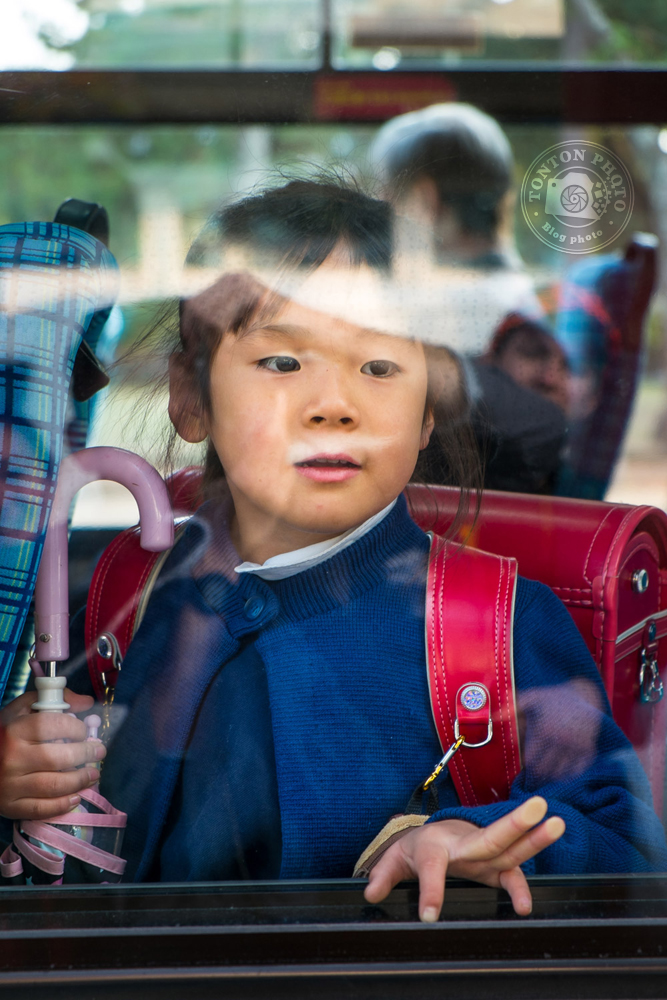 Écolière saluant sa camarade restée à l'arrêt de bus. Nara, Japon © Clément Racineux / Tonton Photo