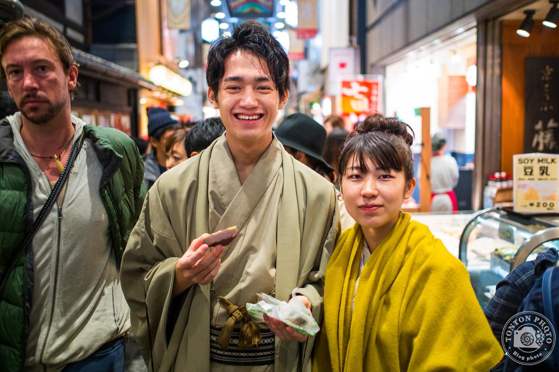 Parfait exemple de photo-bombing ! L'homme sur la gauche est passé tellement vite au moment du déclenchement que je ne l'ai découvert qu'au post-traitement ;) Portrait d'un jeune couple croisé dans la foule du marché de Kyoto, Japon © Clément Racineux / Tonton Photo