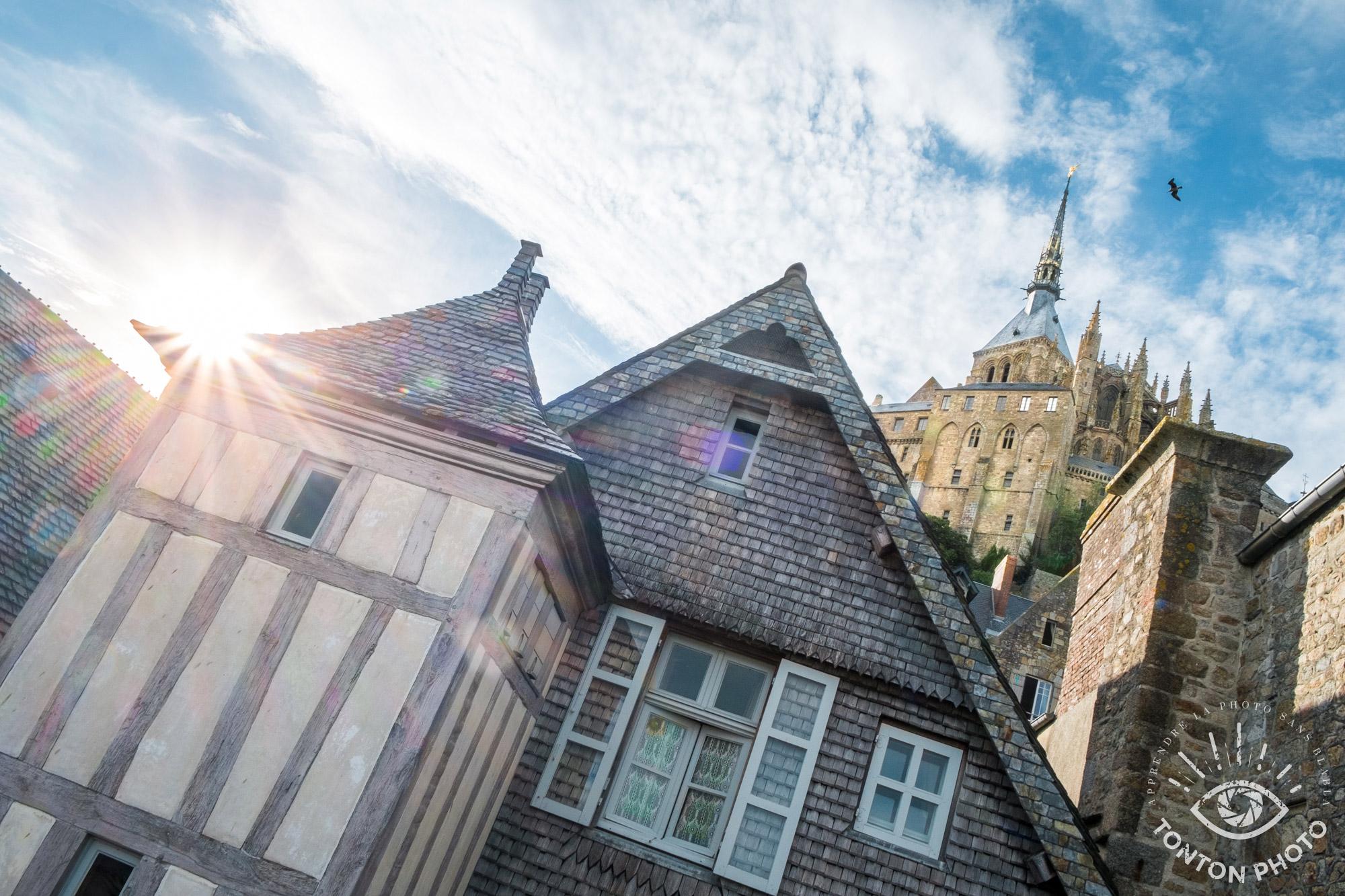 En cachant partiellement le soleil derrière les habitations, j'ai pu capturer les rayons du soleil de manière à dynamiser la photo. Mont Saint Michel, Normandie © Tonton Photo