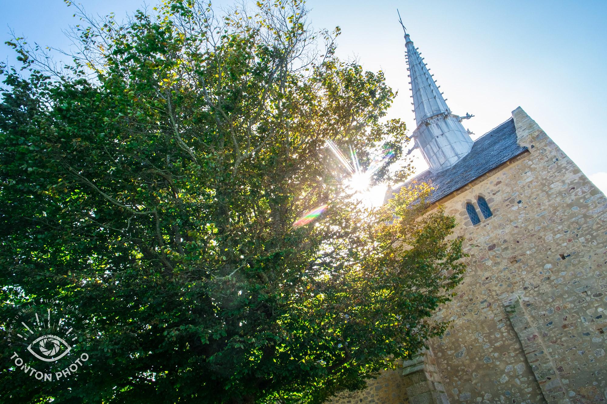 En cachant partiellement le soleil derrière l'église et l'arbre, j'ai pu capturer les rayons du soleil de manière à dynamiser la photo © Tonton Photo