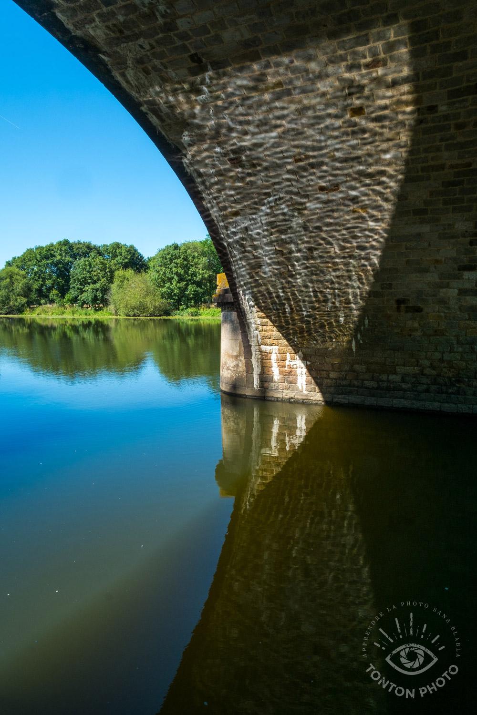 Le long du canal de Nantes à Brest, en observant autour de moi j'ai repéré ce très beau jeu d'ombre et de lumière qui dessinait des lignes courbées sur le pont et son reflet... © Tonton Photo