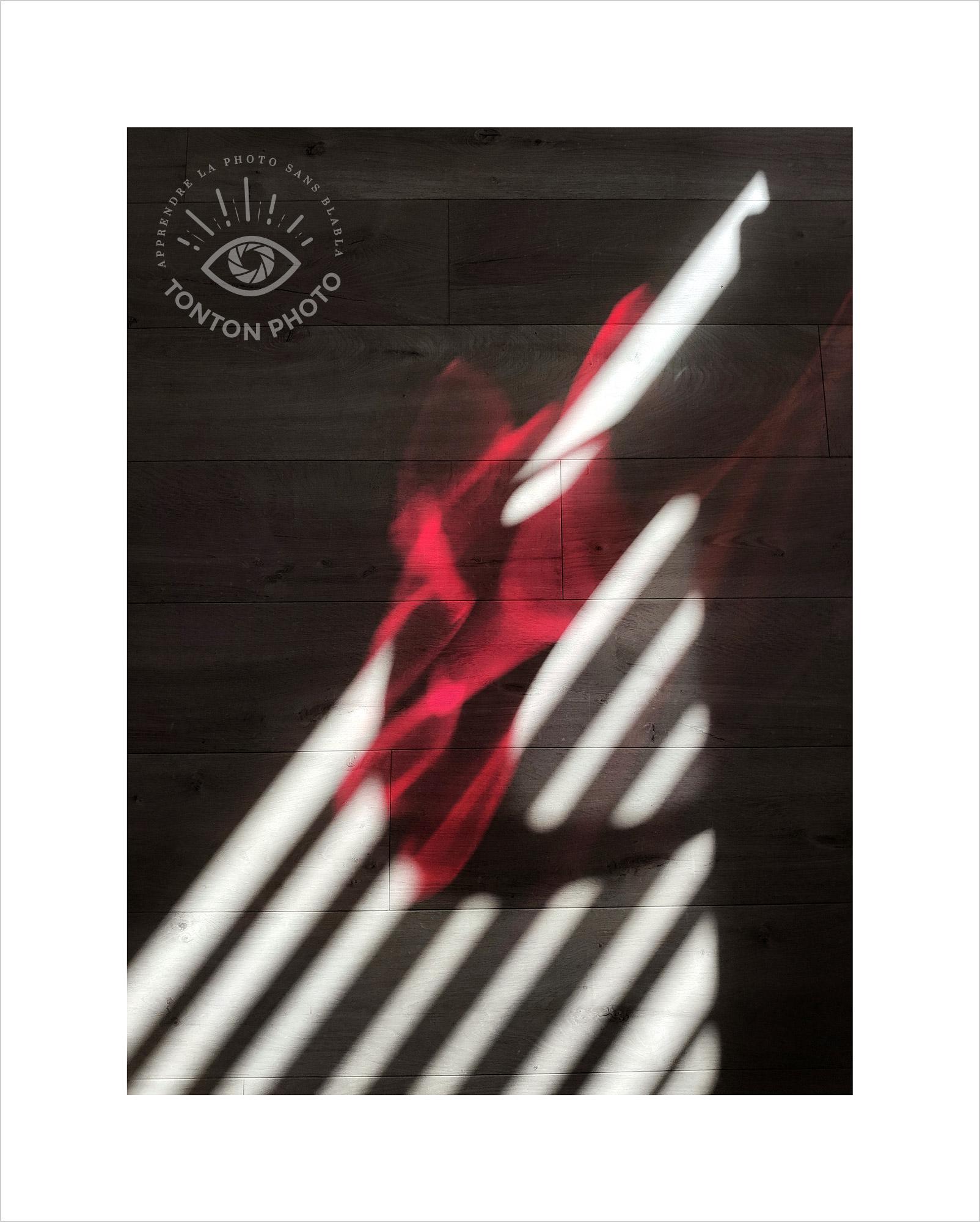 Jeu d'ombre et de lumière projeté sur le sol à travers les rideaux et une chaise translucide rouge. Photo prise au smartphone Xiaomi Mi Mix 3 © Tonton Photo