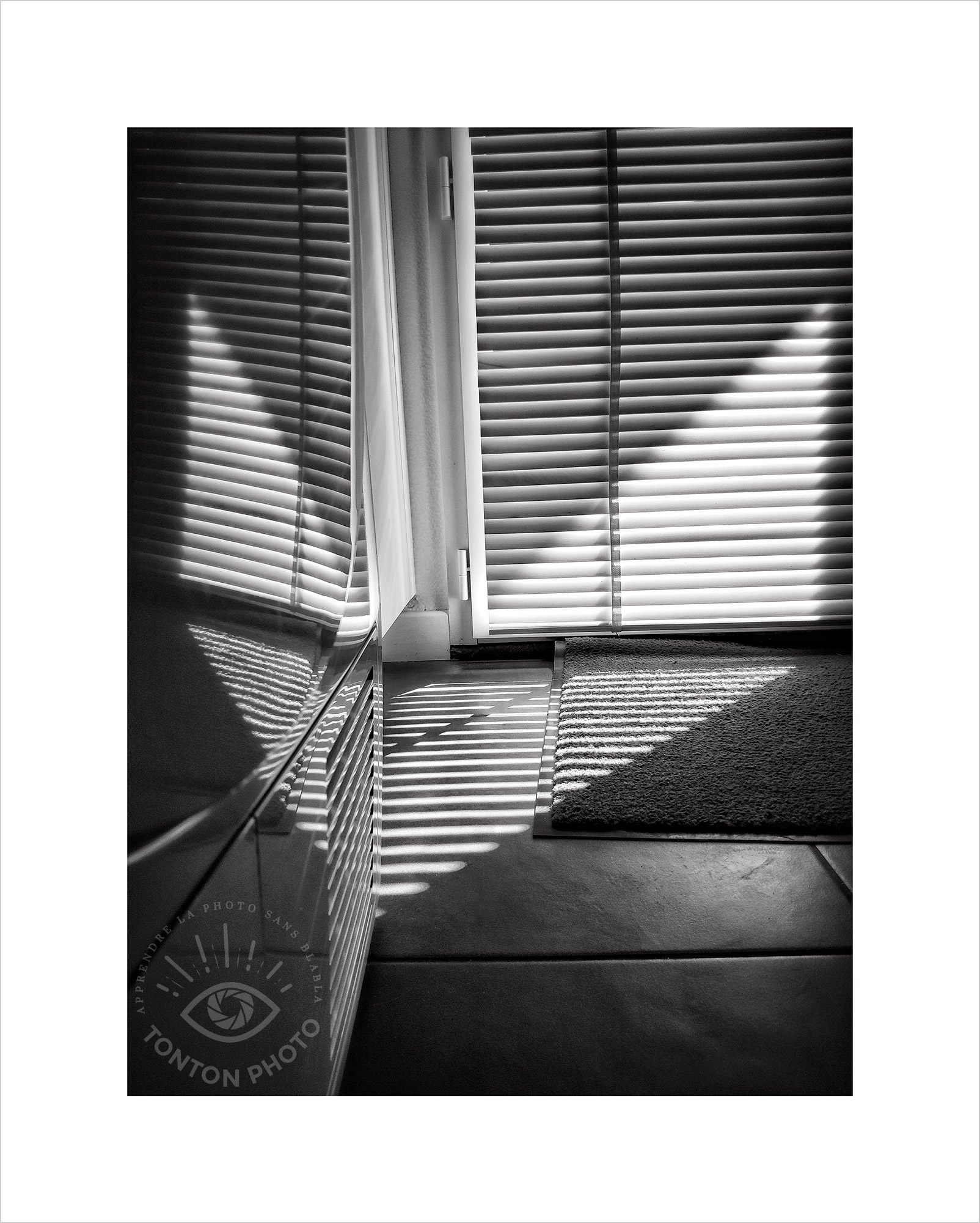 Jeu d'ombre et de lumière  entre les lignes du store, le reflet dans le sèche-linge et les lignes de la grille d'aération de ce dernier. Photo prise au smartphone Xiaomi Mi Mix 3 © Tonton Photo