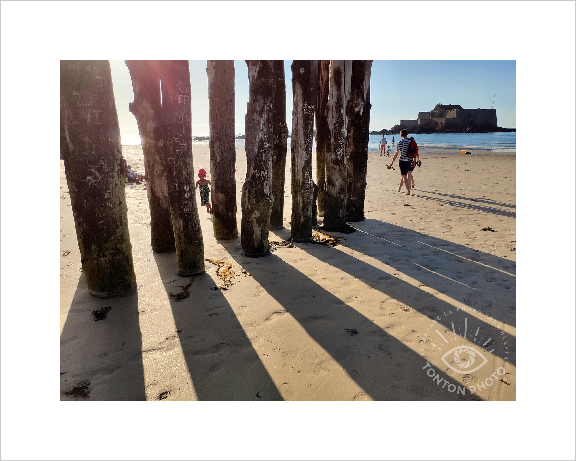 Jeu d'ombre et lumière en fin de journée sur les brise-lames d'une plage de Saint-Malo. Notez que, pour soigner ma composition, j'ai bien attendu que l'enfant passe entre les pieux. Photo prise au smartphone Xiaomi Mi Mix 3 © Tonton Photo