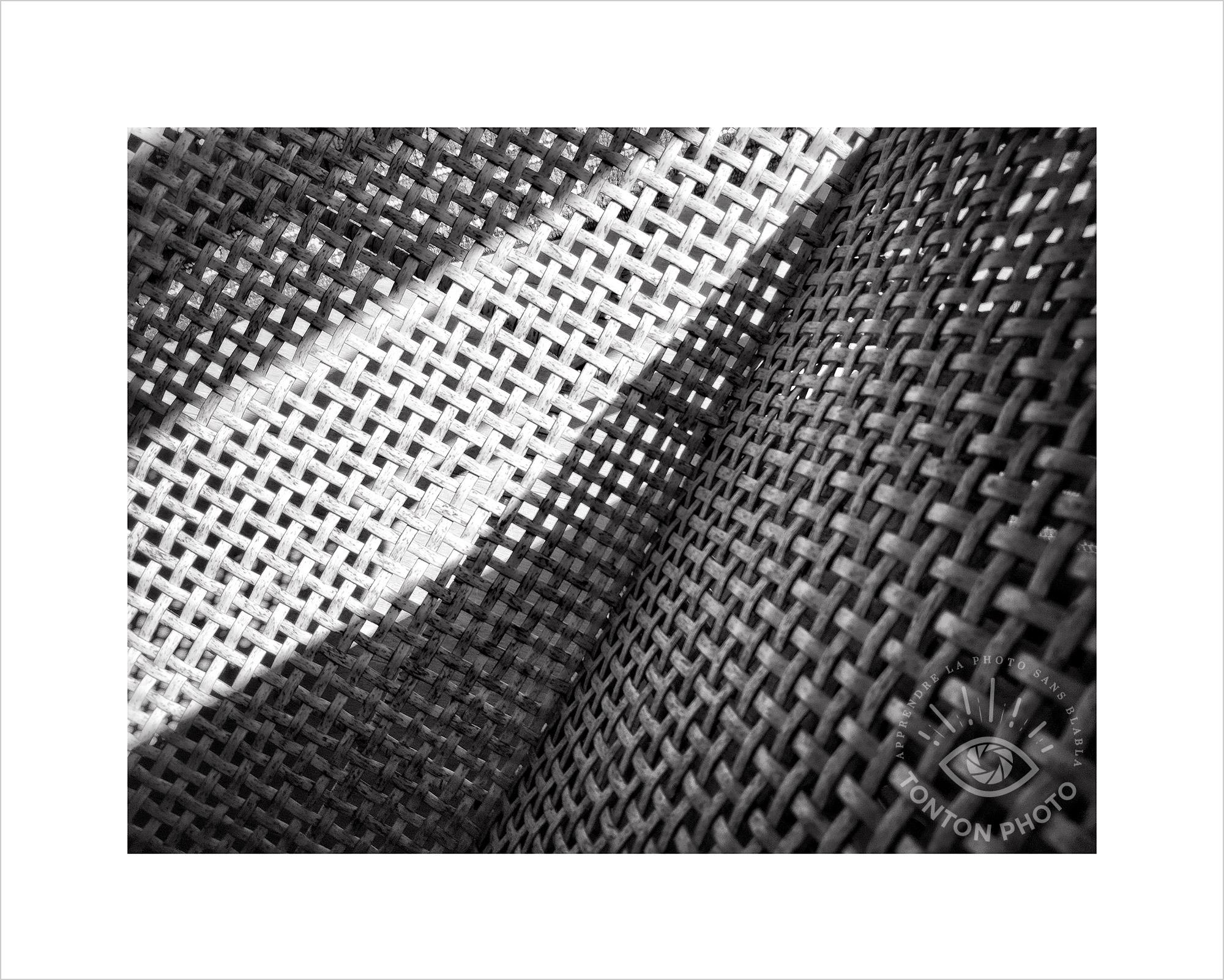 Jeu d'ombre et de lumière : les rayons du soleil sont projetés sur une chaise tressée. Je l'ai photographiée d'au-dessus et cadrée de manière à jouer avec les lignes multiples et les formes. Photo prise au smartphone Xiaomi Mi Mix 3 © Tonton Photo